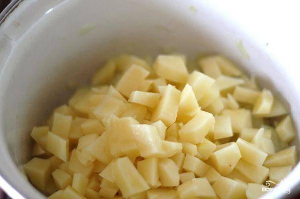 Затем к луку добавить картофель. Овощи постоянно перемешивать, чтоб они хорошенько пропитались маслом, в последнюю очередь закинуть в кастрюлю чеснок.