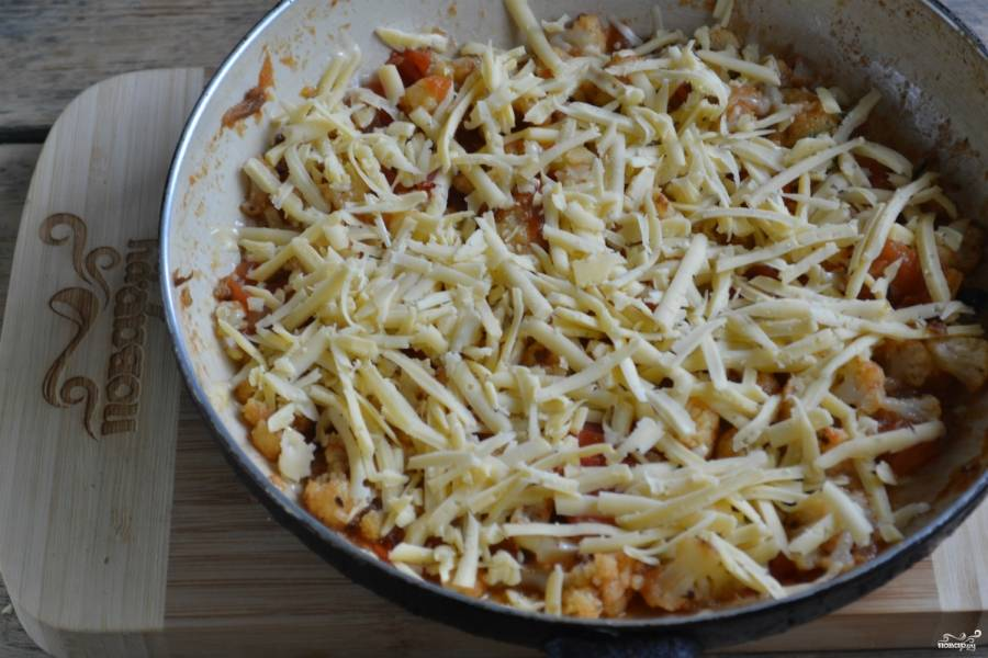 Сыр натрите на крупной терке, посыпьте им цветную капусту с помидорами. Не перемешивая, накройте крышкой и оставьте на медленном огне на 4-5 минут, чтобы сыр расплавился.