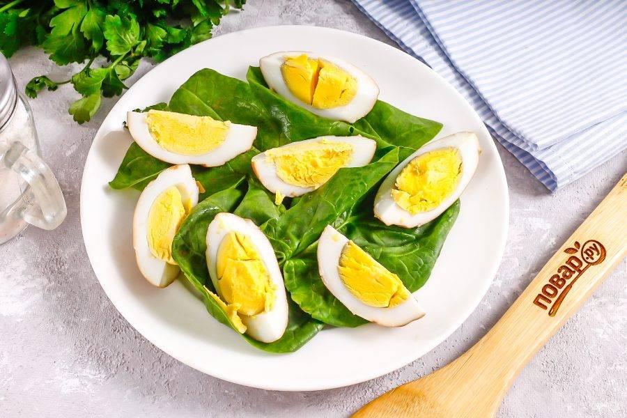 Выложите сметану на листья. Нарежьте копченые яйца на четвертинки и выложите на свежую зелень.