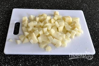 1. Поставьте кастрюлю с водой на огонь, доведите ее до кипения, добавьте рис и варите его на среднем огне. Нарежьте очищенный картофель на небольшие кубики и добавьте в воду.