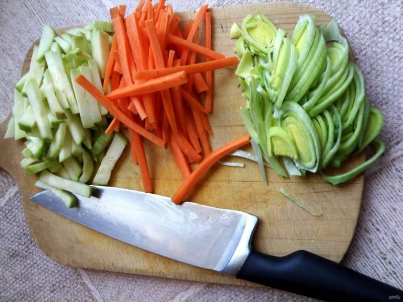 Овощи помойте, обсушите и нарежьте.  Кабачок и морковь брусочками, а лук-порей – кольцами.