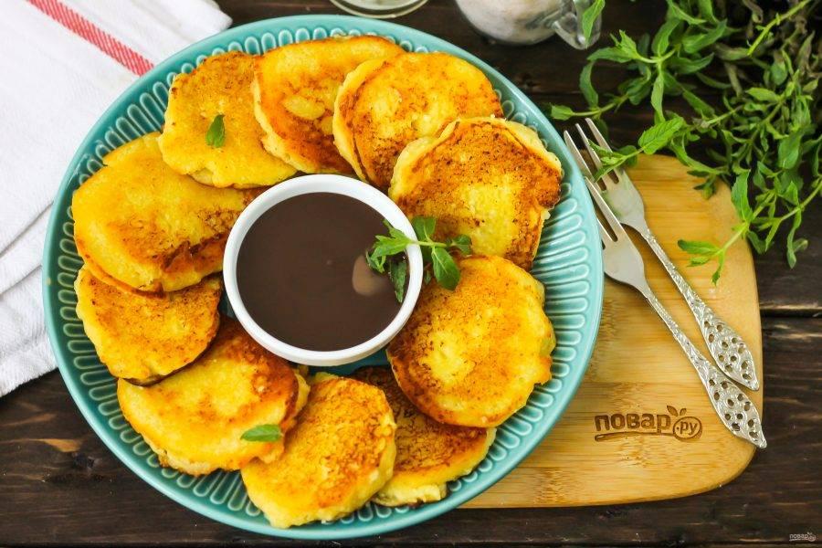 Выложите теплые сырники на тарелку и подайте к столу со сладким соусом, топингом.