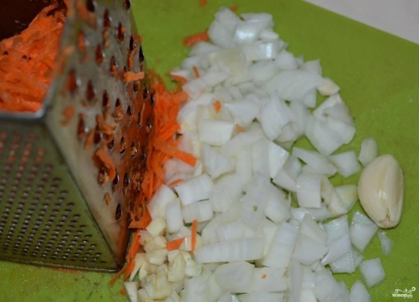 Очистите лучок, морковку и чеснок. Лук порубите, морковь натрите при помощи терки, а чеснок просто придавите плоской стороной ножа. Томаты откройте и протрите через сито.