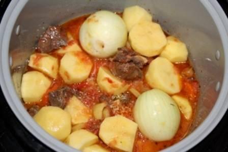 Через 5-6 минут выключаем мультиварку и выкладываем в чашу картофель, нарезанный на довольно крупные куски, а также целые очищенные луковицы.