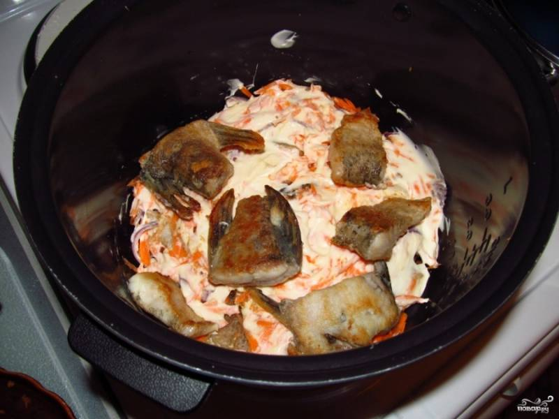 Выкладываем половину кусков рыбы в мультиварку, затем — половину лука и моркови. Посыпаем приправой и майонезом. Потом делаем второй слой, только уже без майонеза.
