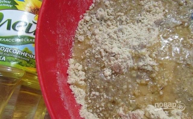 Воду налейте в кастрюльку и поставьте ее на плиту. Разогрейте жидкость на медленном огне, затем всыпьте сахар и размешивайте, пока он не раствориться. Влейте в сироп растительное масло и выключите огонь. Получившимся сиропом залейте муку с орехами и семечками, перемешайте.