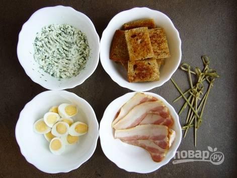 5. Сыр соедините с зеленью и перемешайте. Яйца аккуратно разрежьте пополам. Когда хлеб будет готов, можно начинать собирать канапе.