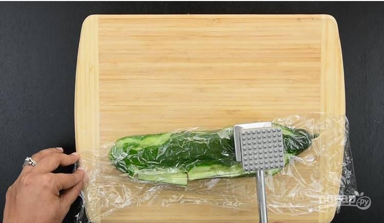 1. Обмотайте огурцы пищевой пленкой и разбейте огурец с помощью молотка.