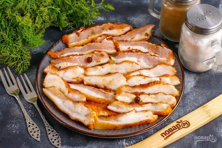 Готовое соленое сало нарежьте тонкими ломтиками и подайте к столу с несладкой выпечкой.