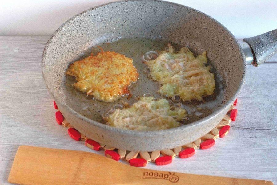 Выкладывайте драники столовой ложкой в сковороду с разогретым расительным маслом. Немного разровняйте и жарьте с двух сторон до готовности. Затем выложите на салфетку, чтобы убрать излишки масла.