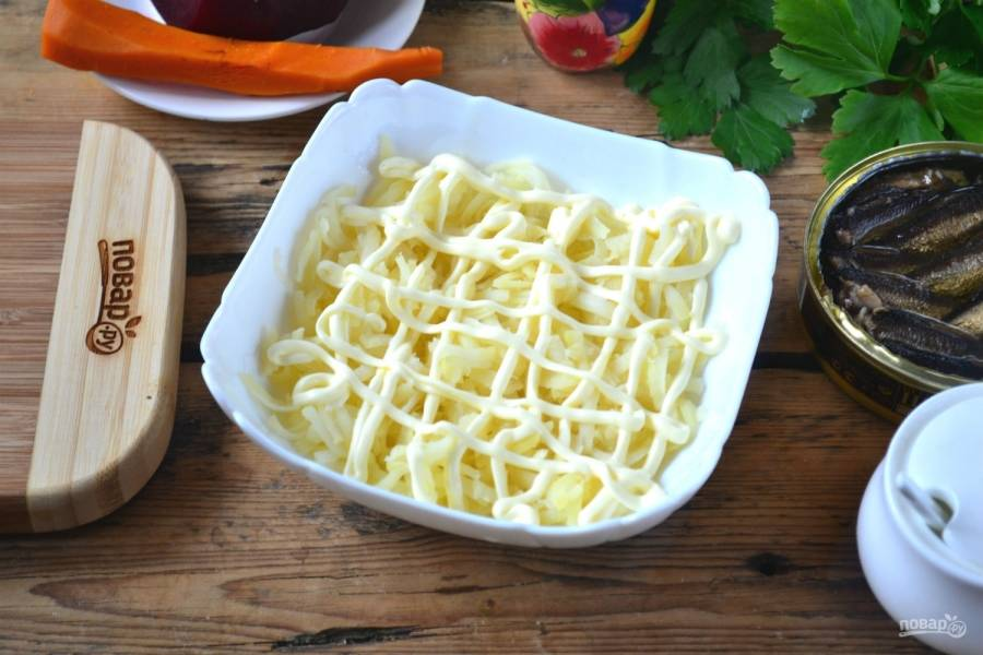 На дно глубокой тарелки выложите натертый на крупной терке картофель. Смажьте майонезом или просто сделайте майонезную сеточку.