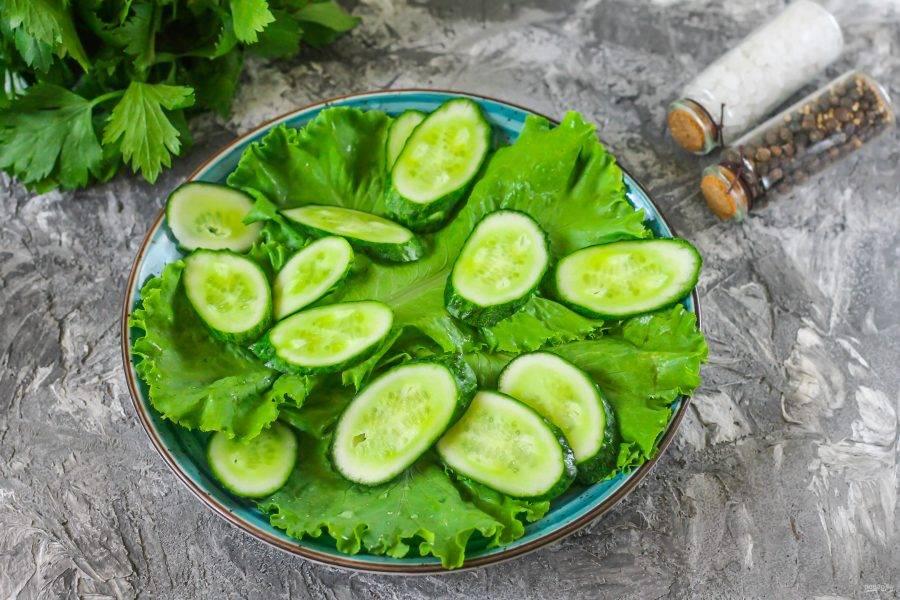 Промойте листовой салат и огурцы, тщательно смывая с поверхности овощей шипы и пыль. Срежьте хвостики с плодов. Нарежьте их слайсами по диагонали, чтобы нарезка выглядела аппетитно. Листья салата высушите и выложите их на тарелку. Следом на салат выложите огуречную нарезку.