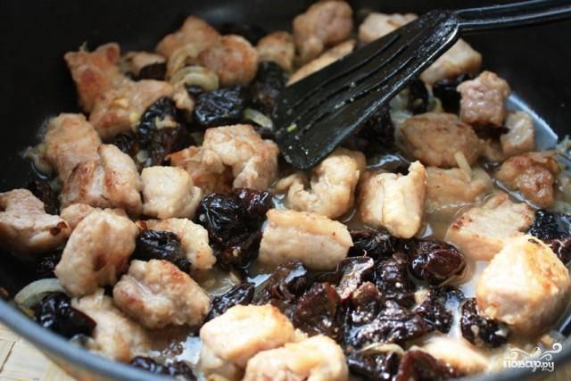 Затем добавляем в сковороду свинину, чернослив (чернослив не режем, добавляем целым) и портвейн. На быстром огне выпариваем весь портвейн, после чего наливаем воду (или бульон), сбавляем огонь и тушим под закрытой крышкой минут 15-20 - пока не выпарится вода.