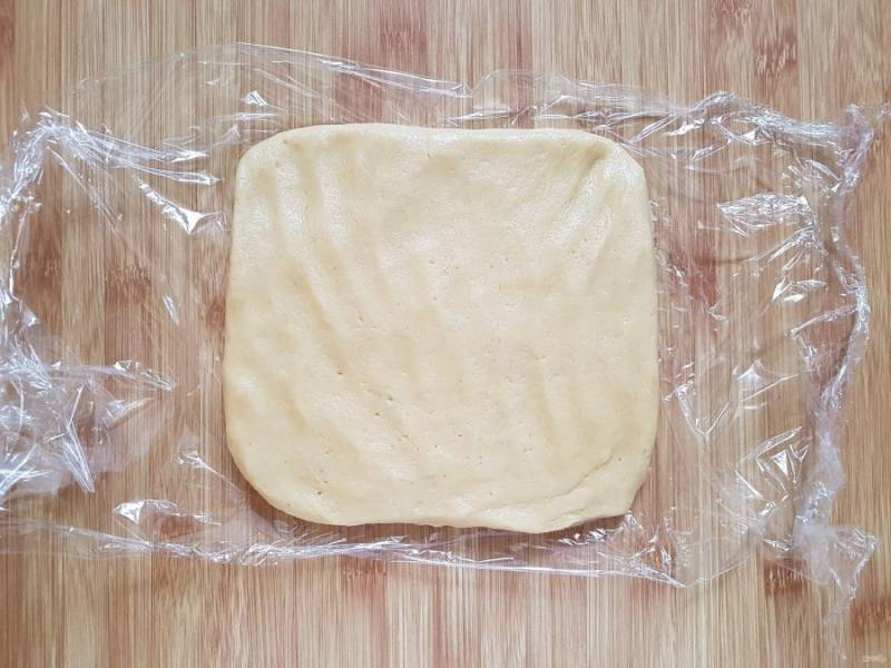 Соберите тесто в шар, затем придайте ему форму прямоугольника и, завернув в пищевую пленку, уберите в морозильную камеру на 30 минут.