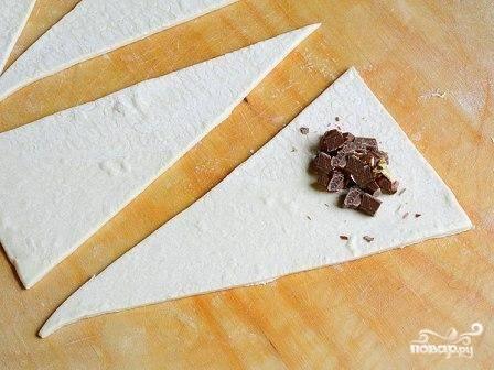 На самую короткую сторону треугольника выложите несколько кусочков шоколада. Чтобы шоколад лучше ломался, отправьте его на некоторое время в холодильник, а потом поломайте на кусочки.