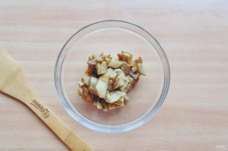 Баклажаны нарежьте половинками кружков или четвертинками и выложите в салатник.