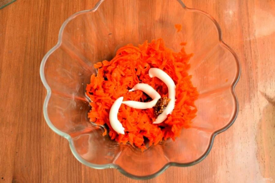Натрите на крупной терке отварную морковь и смешайте ее с толченым чесноком и зернистой горчицей. Посолите смесь по вкусу, добавьте немного майонеза и перемешайте. Выложите в посуду с блинчиками ровным слоем, хорошо утрамбовывая.