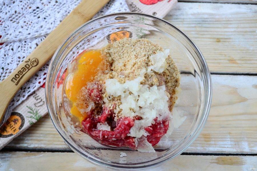В большой миске смешайте говяжий фарш, яйца, панировочные сухари и мелко порубленный лук. Посолите и поперчите по вкусу.