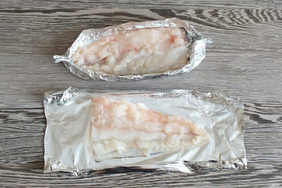 У слегка подмороженной рыбы удалите хребтовую кость. Удалите все возможные косточки. Филе разрежьте на части. На небольшой лист фольги выложите один кусочек филе и сформуйте лодочку.