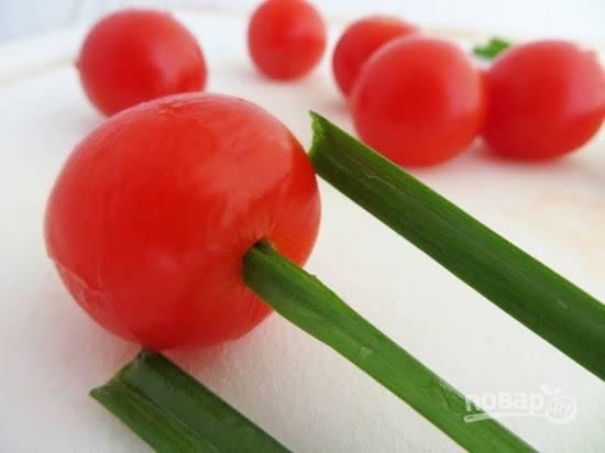 4. Аккуратно поместите начинку в помидорки. Перья лука вымойте, обсушите и вставьте в отверстие снизу.