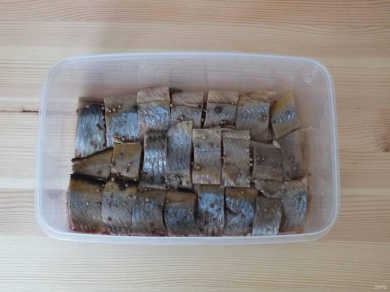 Возьмите широкую форму. Очень важно, чтобы сельдь поместилась в один слой. На дно формы раскрошите лавровый лист. Выложите нарезанную сельдь (кусочек не более 40 грамм), пересыпая кориандром и душистым перцем.