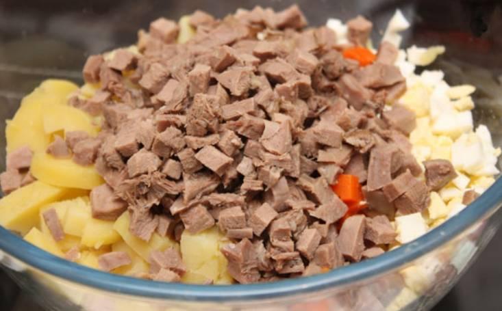 Сваренный говяжий язык режем мелкими кубиками и добавляем в салатницу.