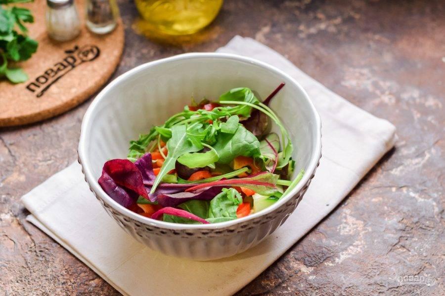 Переложите овощи в миску, добавьте следом салатный микс.