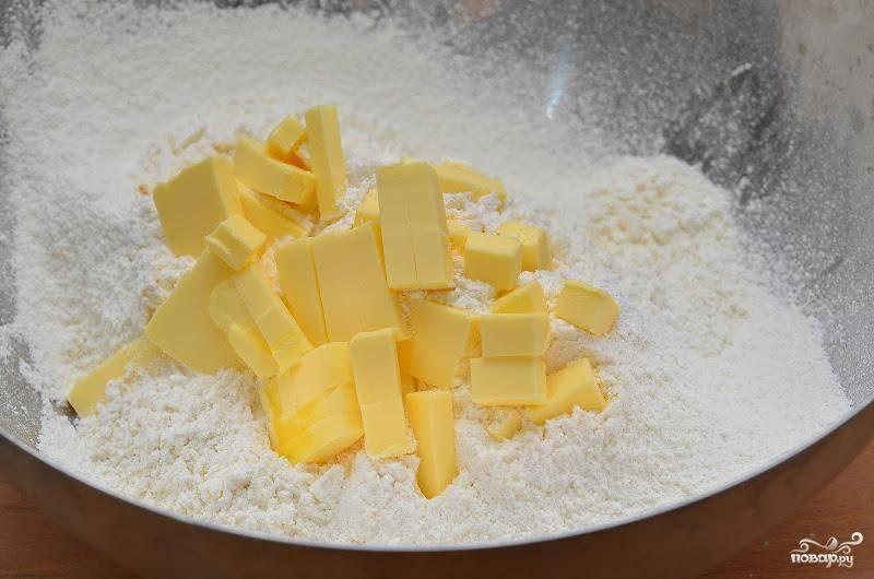 К муке добавляем на кубики нарезанное сливочное масло.