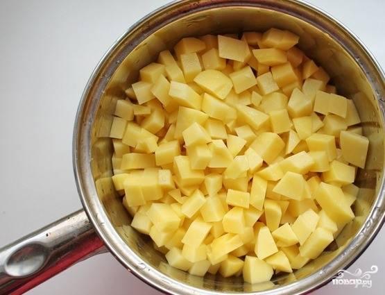 Пока отваривается белая фасоль, вам необходимо заняться картофелем. Очистите его от кожуры и нарежьте на небольшие кубики. Затем сложите в дуршлаг и промойте большим количеством проточной холодной воды. Таким образом вы избавитесь от ненужного крахмала.