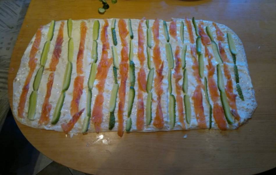 2. Выкладываем теперь поверх сыра кусочки рыбы и огурцов, добавим немного салатных листьев и зелени, заворачиваем в рулет.