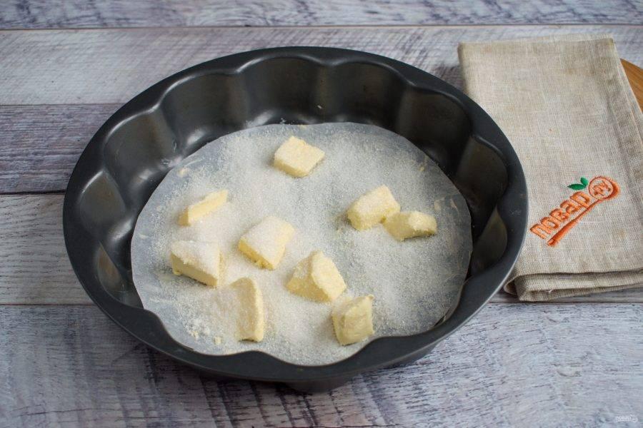 Дно формы  (диаметр - 20 см) простелите пергаментом для выпечки. Высыпьте 1/2 стакана сахара, разложите кусочки сливочного масла.