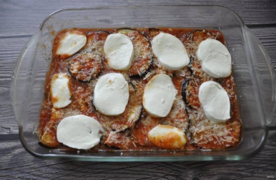 Повторите еще слой томатного соуса, баклажанов и пармезана, сверху выложите кружочки моцареллы.