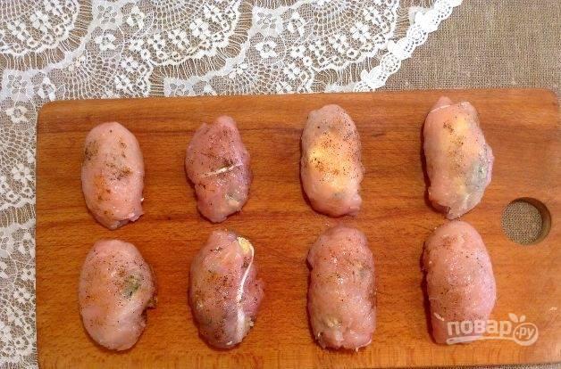 Влажными руками заверните котлетки по-киевски так, чтобы они не развалились. Снаружи промажьте все изделия перцами.