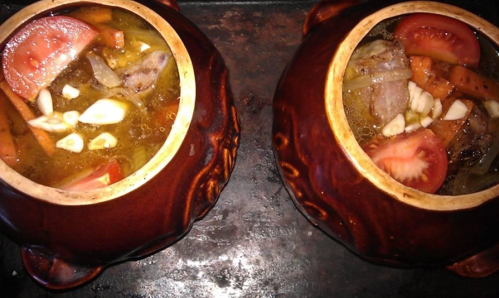 Через час достаем горшочки, кладем в них нарезанные дольками помидоры и измельченный чеснок. Отправляем в духовку на 20 минут.