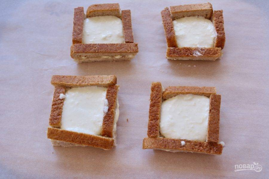 Сырную массу посолите и поперчите. Выложите в каждый квадратик. У меня на 1 тост ушло 1,5 ст. ложки сырной массы. Действуйте быстро. По мере остывания масса густеет.