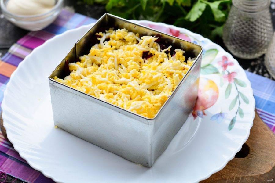 Присыпьте салат тертыми яйцами и готово. Салат поставьте охладиться на 15 минут в холодильник.