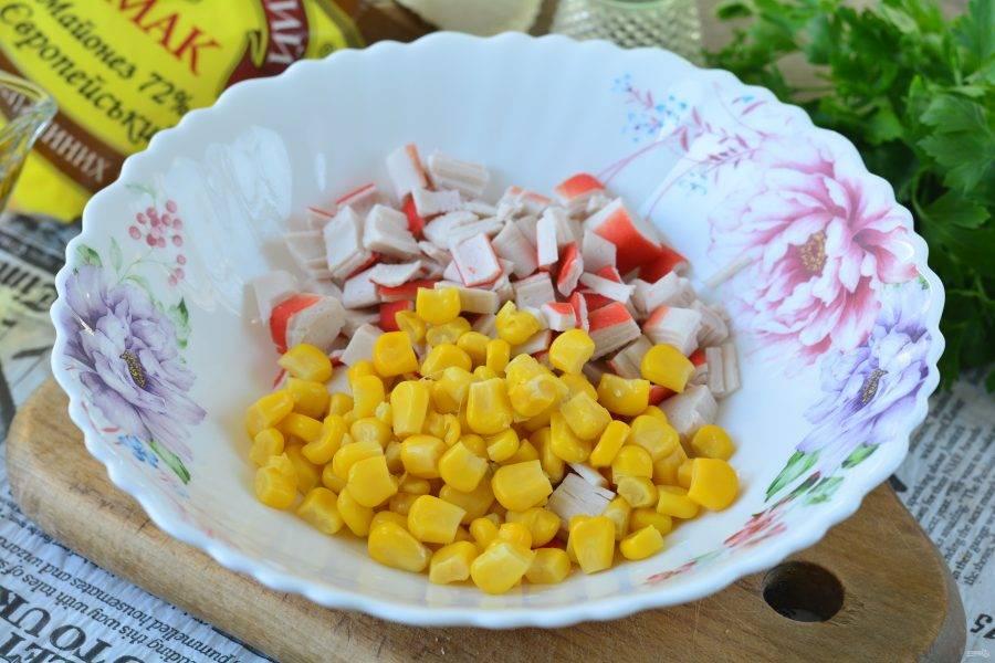 Смешайте крабовые палочки с консервированной кукурузой.