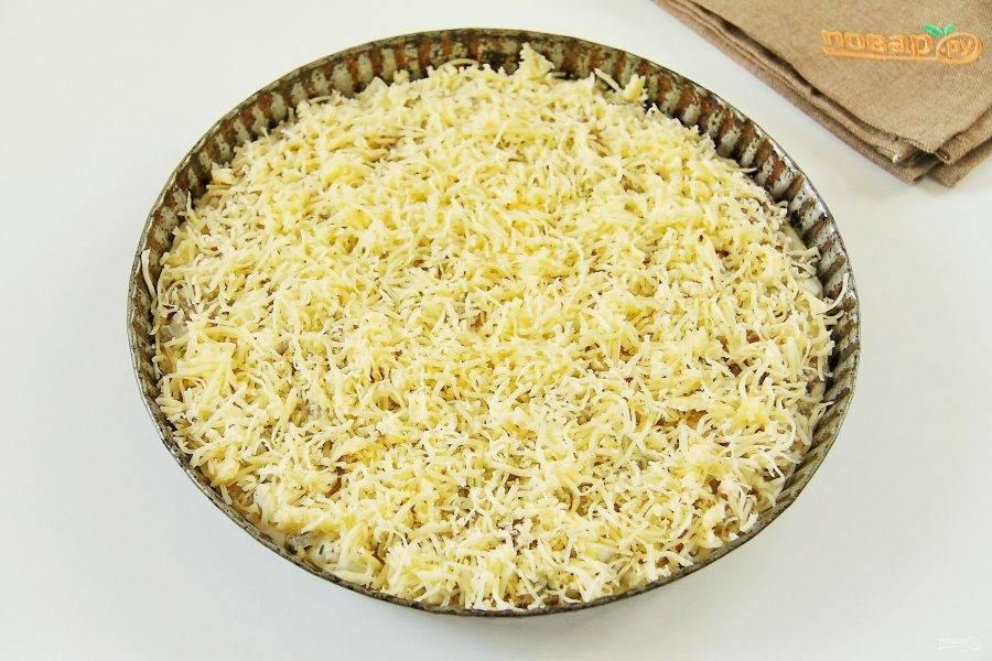 Посыпьте все тертым сыром и выпекайте пирог при 180 градусах около 30 минут.