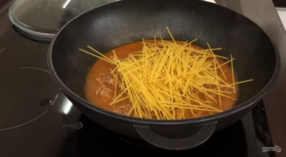3. Добавьте воду, накройте сковороду крышкой и на среднем огне проварите фрикадельки 15 минут. Спагетти слегка поломайте и добавьте к готовым фрикаделькам.