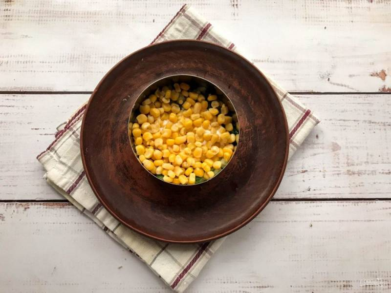 Сверху огурцов выложите консервированную кукурузу.