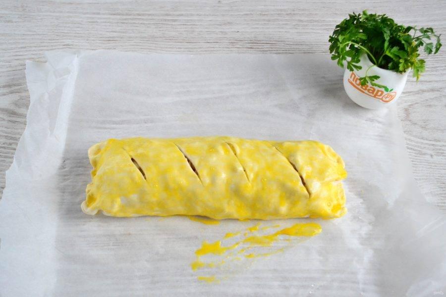 Заверните тесто с начинкой в рулет, сверху сделайте несколько надрезов. Смажьте рулет взбитым яйцом.