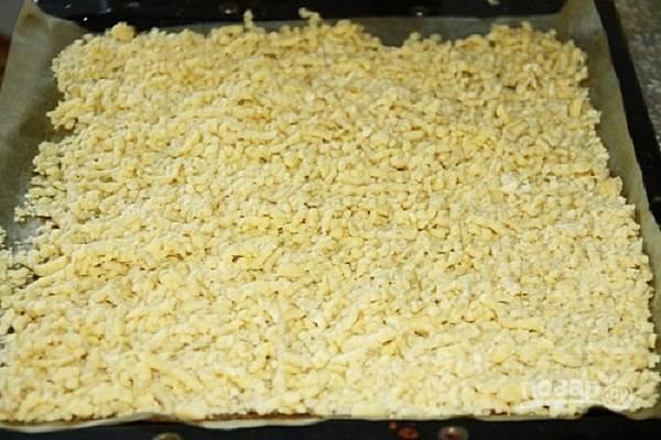 Натираем тесто на крупной терке (или пропускаем через мясорубку с крупной решеткой) на противень и отправляем запекаться в разогретую до 180-200 градусов духовку до красивого золотисто-коричневого цвета.