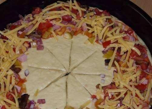 Смазать края теста кетчупом и разложить начинку. Сверху посыпать тертым сыром.