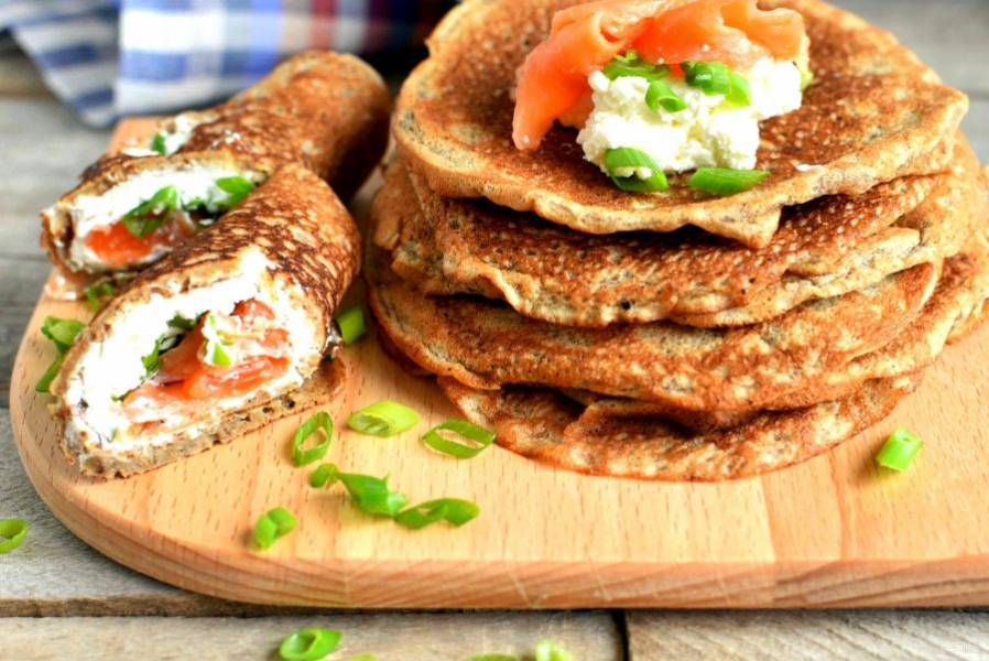 При подаче намажьте блинчик сыром, посыпьте зеленым луком , уложите сверху немного форели и сверните рулетиком.