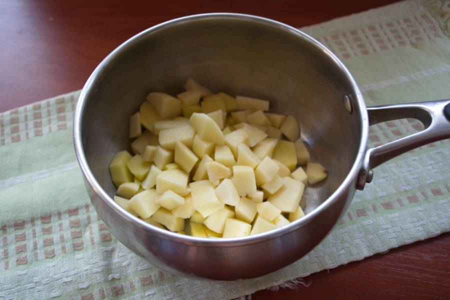 В кастрюлю поместите очищенный картофель, который необходимо нарезать на кубики. Залейте его водой и поставьте вариться.