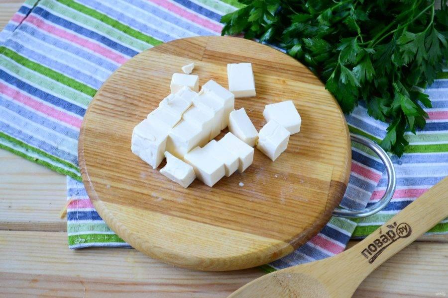 Мягкий плавленый сыр порежьте на кубики, так ему легче будет расплавиться в супе.