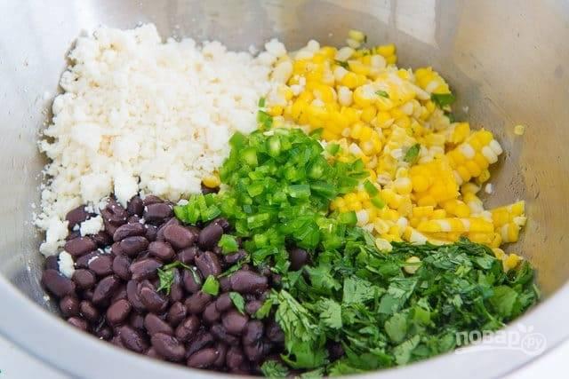 2. Теперь мелко нашинкуйте кинзу и перец. Затем смешайте их с фасолью и кукурузой. Также добавьте рассыпчатый сыр.