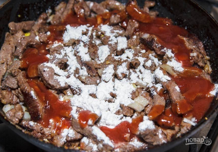 Потом влейте соус. Обжарьте мясо ещё 3 минуты, и всыпьте муку.
