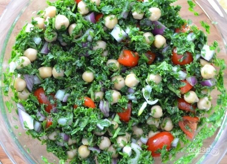 4.Нарежьте кубиками помидор и лук, выложите к зелени, слейте воду с консервированного нута, по вкусу добавьте соль и перец. Подавайте салат сразу или охладите.