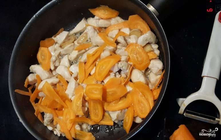 Морковь очищаем и нарезаем тонкими пластинками. Добавляем к курице, готовим еще 5-6 минут.